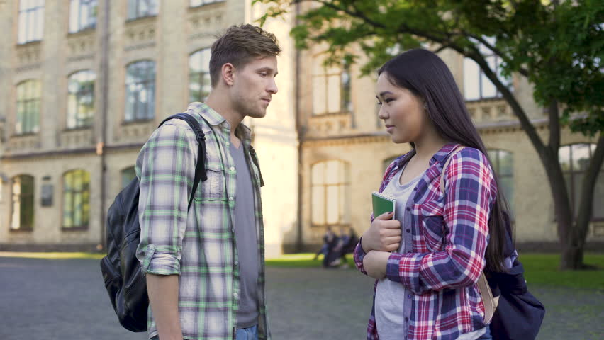 student trying to talk with his asian girlfriend near college