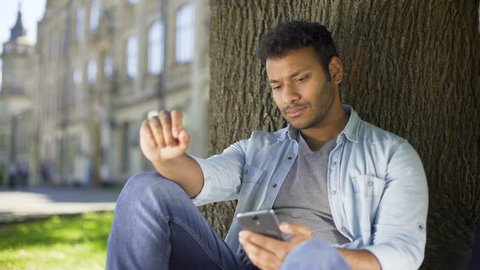 College student reading newsfeed on phone, getting disappointed with news, upset