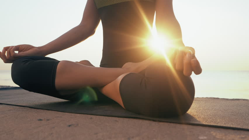 Young caucasian woman in bodysuit relaxing by practicing yoga on the beach near calm sea, close-up of hands, gyan mudra and lotus position. Sunrise background. Slow motion. | Shutterstock HD Video #29186872