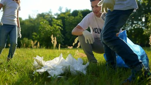 Excited kids collecting paper napkins into garbage bag while volunteering