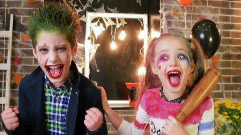 harley quinn and joker screaming, kids having fun at halloween party, crazy characters, spooky makeup,