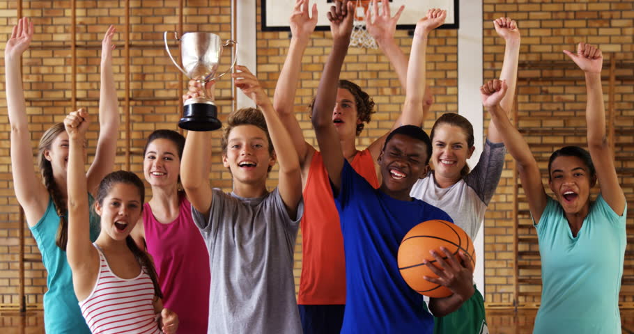 Group of high school kids cheering while holding trophy in basketball court