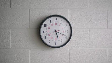 Analog clock in school classroom hallway on wall telling time