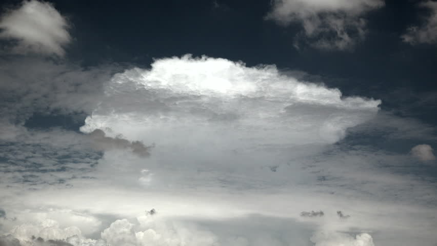 Time Lapse, Striking, sunlit monsoon anvil cloud rises like spaceship amid swirling darker clouds, blue sky. 4K UHD 3840x2160