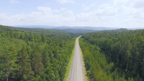 AERIAL: The flying camera is moving backwards along curved asphalt road among the pine forest. Cars are traveling at a distance. Amazing background with blurry mountains, blue sky and white clouds.