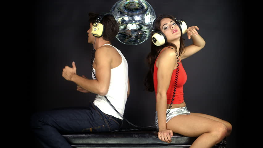 young couple listening to music on headphones, posing and flirting together