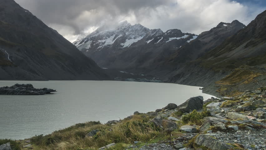 Time Lapse - Clouds moving at Mount Cook with Hooker Lake as foreground. Captured during rain, water droplets on lens. Camera pan left.