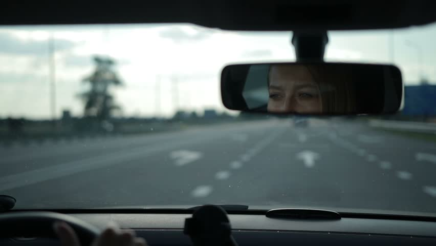 Reflection of lovely woman in car rear-view mirror | Shutterstock HD Video #29258683
