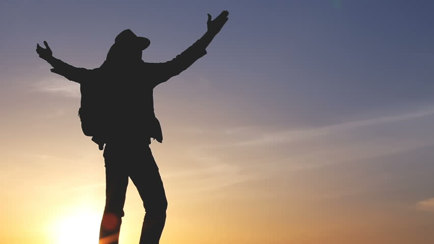 Man reaching the top and cheering hands raising to the sky in slow motion Success Pose by Man on Top of Hill Lifting Hands toward Sun Color Background silhouette City Skyline | Shutterstock HD Video #29259412