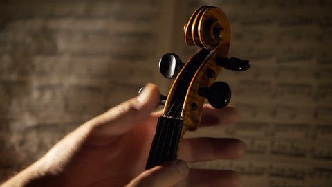 Violinist's hands tuning a violin before the perfomance. Close up shot with dramatic concert lighting and musical notes on background. 4K, UHD