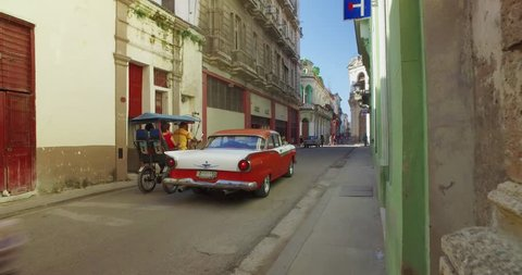 HAVANA, CUBA - Circa July, 2017 - A tracking POV dolly establishing shot walking in the narrow streets behind a classic car in Havana's old town district.
