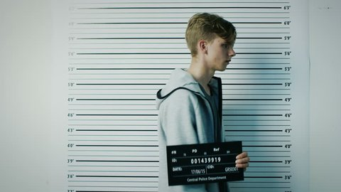 In a Police Station Arrested Teenage Delinquent Steps in for Side, Front View Mugshot. He is Heavily Bruised. Height Chart in the Background. Shot on RED EPIC-W 8K Helium Cinema Camera.