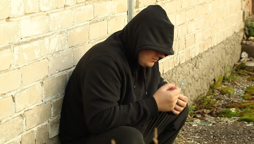 Drug addict man leaning against the wall