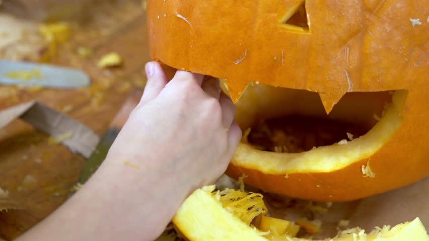 Child working on pumpkin for Halloween