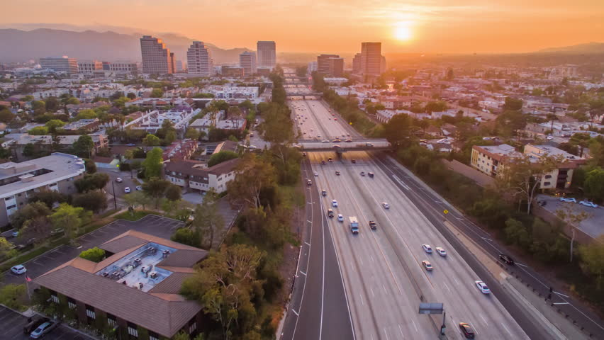 Aerial timelapse in motion (hyperlapse) overhead shot at sunset in LA at twilight with the sky changing from day into night with golden skies. Sun sets behind city skyline and high rise buildings.