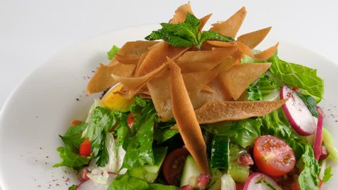 Traditional Arabic fattoush salad with pita bread, fresh vegetables and herbs mixed with vegetables, loop, 4K, ProRes codec, 422 HQ, ISO 100