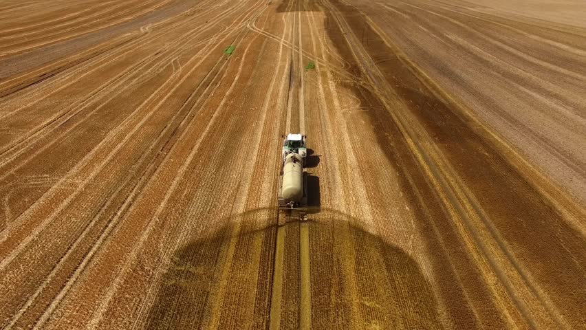 aerial view of a tractor with a trailer fertilizes a freshly plowed agriculural field with manure in germany