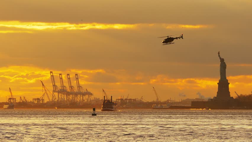 Beautiful sunset over New York Upper Bay and Statue of Liberty with ferry boat and flying helicopter