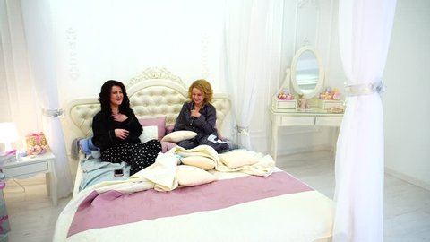 Funny girls read funny message on mobile and postponing gadget to side begin to burst into laughter and smile, sitting on large and beautiful four-poster bed in light and spacious maid's bedroom with
