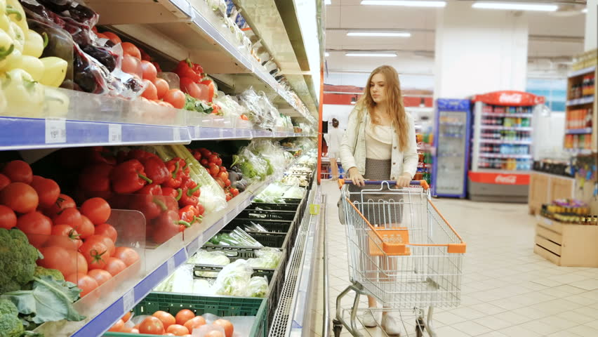 TERNOPIL, UKRAINE - JULY 15, 2017: Woman grocery shopping. Young woman chooses vegetables on store shelves. | Shutterstock HD Video #29430283