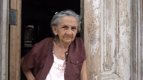 TRINIDAD, CUBA - FEBRUARY 2017: Portrait of a senior Cuban woman, standing at the door of her home in Trinidad