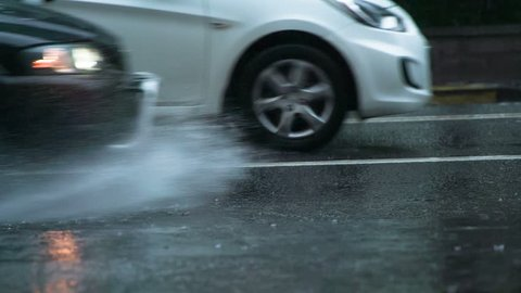 Rain in Rush Hour. The car moves past the camera and rides through the puddle. From under the wheel rises a beautiful stream of water. Filmed at a speed of 240fps