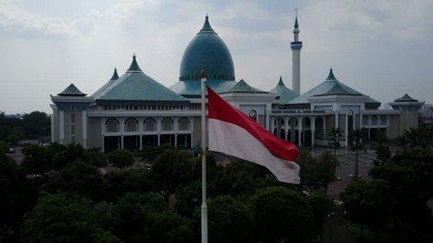 SURABAYA, INDONESIA - APRIL 2017: Drone shot of waving Indonesian national flag revealing Al Akbar mosque in Surabaya