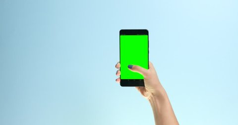 Closeup hand with a smartphone with chromakey display screen making swipe on colorfull background