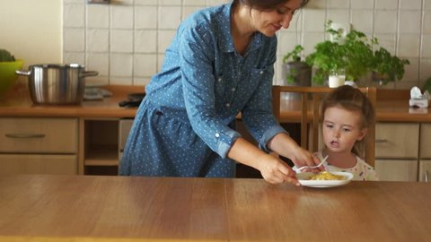 Mother and daughter having healthy breakfast in kitchen. The girl is not hungry. She refuses to eat, pushes the plate aside. Poor appetite.