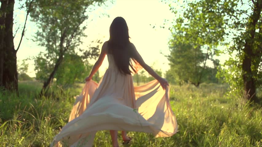 Beauty romantic young woman in long chiffon dress with gown running in the forest on sunset. Beautiful happy bride model girl enjoying nature outdoors. Slow motion 240 fps. High speed camera 4K UHD