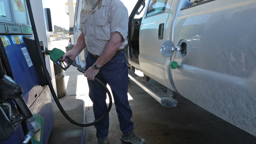 Man filling pickup truck with gas. Person at station re fuel for a road trip. Expensive cost of living caused by environmental regulations. Need for USA to become energy independent.