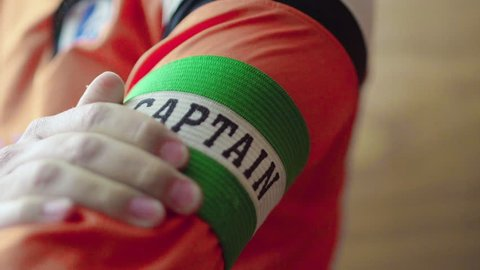 Captain puts armband on sleeve. Sports captain wears his armband with pride ahead of match, preparation before big game.