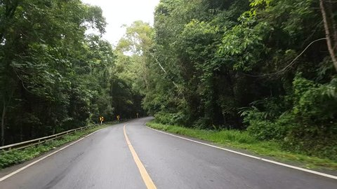 Driving along a curving road through the Inthanon mountain and forest in Thailand in the morning