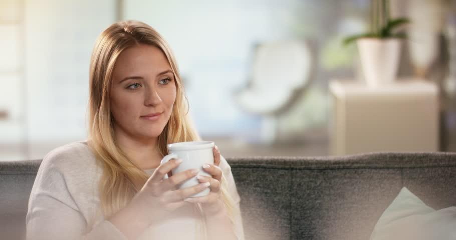 Beautiful young woman enjoying a cup of tea while sitting on coach   Shutterstock HD Video #29587252