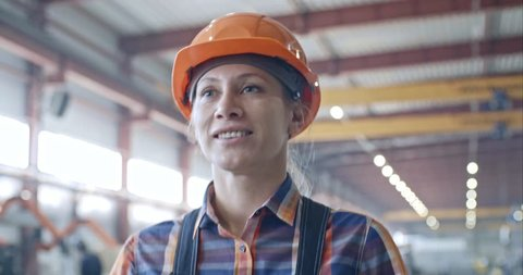 Tilt down of beautiful female factory worker walking through industrial building, holding welding mask and smiling