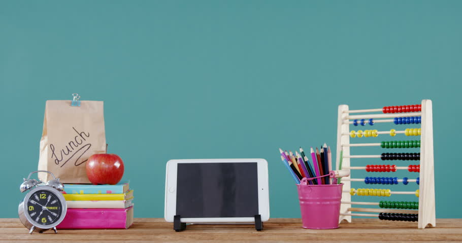 School accessories with digital tablet, lunch and alarm clock on table against green background | Shutterstock HD Video #29611684