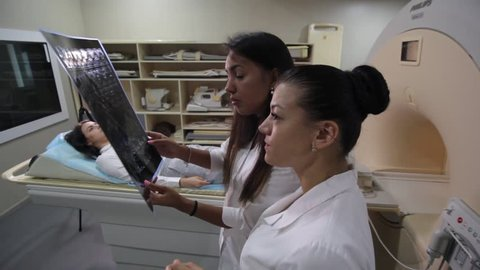 VINNITSA, UKRAINE, JULY 27, 2017: Medical technical assistant councelling patient and preparing scan of the knee with magnetic resonance tomography MRI in radiology.