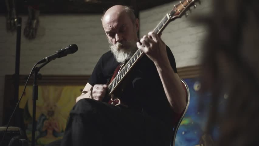 An elderly man with a gray beard skillfully plays the electric guitar, the guitarist plays against the background of abstract paintings, a seven-stringed electric guitar, a man plays with inspiration  | Shutterstock HD Video #29646562