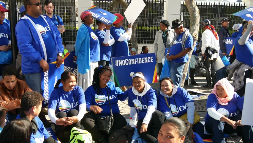 CAPE TOWN SOUTH AFRICA, 8 AUGUST 2017, street demonstrations on day of Zuma no confidence vote in parliament, women DA protesters dressed in blue sit on pavement raise hands and smile.