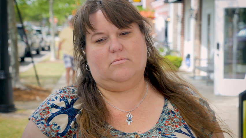 A depressed and sad attractive overweight woman standing outside a city shopping district in a city or modern commerce mall in spring or summer during the day