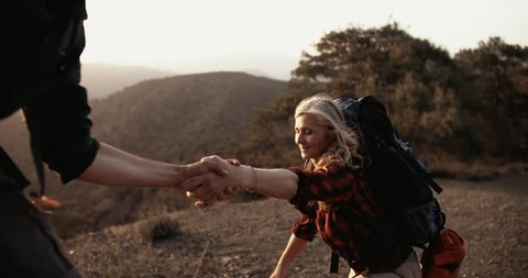 Mature woman on a hikinig adventure holding man's hand helping her climb on mountain hill