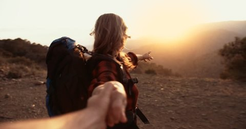 Senior woman hiker holding husband's hand and reaching mountain peak with panoramic view at sunset