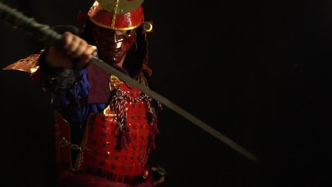 A samurai man in a beautiful red armor and a red defensive mask of a demon pulls the katana out of the sheath and holds it in his hands