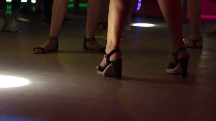 Girls are dancing in a nightclub. Beautiful legs on heels close-up.