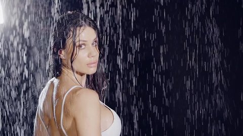 close-up. portrait of attractive woman in a dark room with the ceiling dripping water jets. she is in wet white dress and looking at the camera