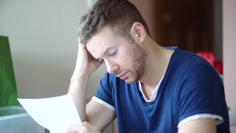 A man in debt is worried and stressed whilst looking through bill letters. Sad and anxious he holds his head in hands. White Caucasian wearing casual clothes in 30's.