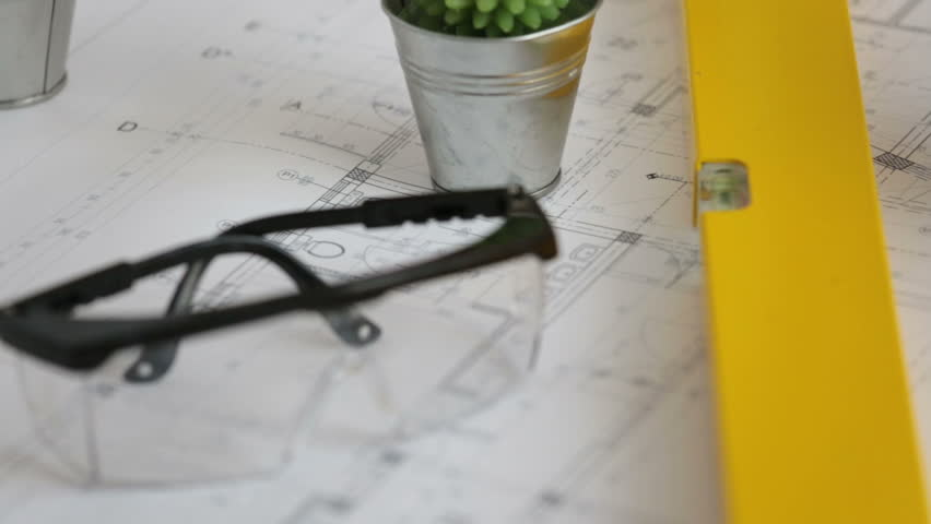 Construction blueprints and protective wear on table | Shutterstock HD Video #29742292