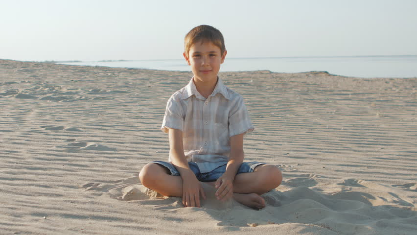 aa915ae97 Portrait of cute boy in a white shirt sits on the sand on a summertime on  the background of the sea