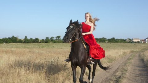 Young girl wearing long red dress riding black horse in countryside. Beautiful horsewoman rides a trotting stallion across a field in slow motion. Girl's long hair and horse mane blowing in the wind.