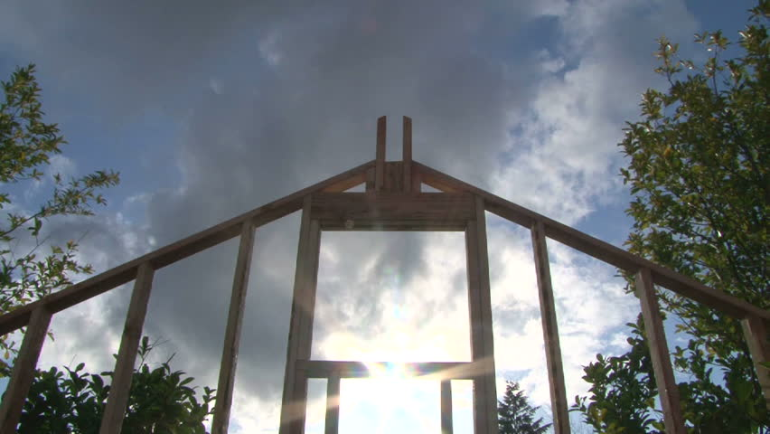 Time Lapse of clouds and sun shining through window on framework of new construction.
